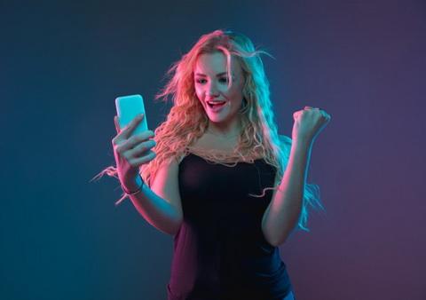Mergina džiaugiasi laimėjimu ir laiko rankose telefoną