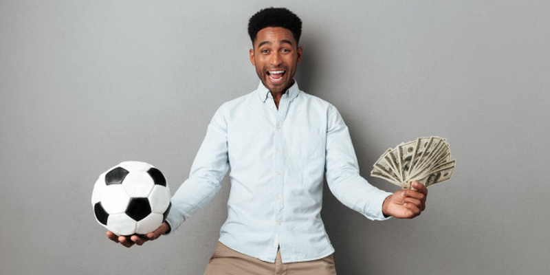 Žmogus laiko kamuolį ir pinigus, nes buvo laimėtos internetinės lažybos